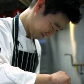 Chef Sung Chul Shim dropping a quail egg on top of Beef Tartare to add delicate taste